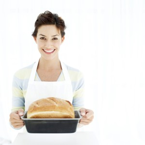 Woman Holding a Baking Tray with Freshly Baked Bread
